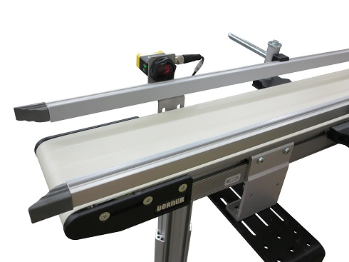 2200 Series conveyor equipped with photo-eyes, a retractable end stop and a pusher